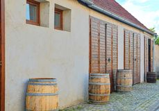 Old rustic wine barrels in front of modern wine cellar. Wine background in Europe. Czech Republic, South Moravia.  stock photos