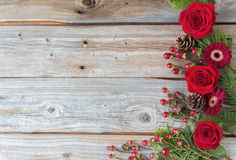 Old rustic wood background with red roses on one side. Stock Photos