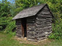 Old rustic wood log outhouse. Stock Photo