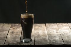 Wood table with black background and craft beer. Old rustic wood table with black background copy space blank craft beer dark brew coffee head poured royalty free stock photos