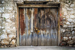 Old rustic wooden doors. Old rustic wooden gate on stone wall Stock Image