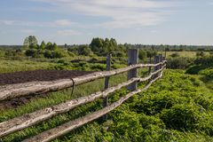 Old rustic wooden fence in the Siberian village, stretching into the distance. stock photo