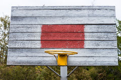 Old rustic wooden outdoor basketball goal. Post without a net and with a colorful yellow hoop royalty free stock images