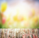 Old rustic Wooden table over blurred flowers garden background Royalty Free Stock Images
