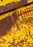 Old rusting metal skip container with yellow pealing paint Stock Photos