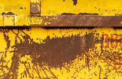 Old rusting metal skip container with yellow pealing paint Stock Image