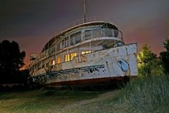 Old rusty abandoned ship on the shore. Light is lit in some windows stock image