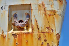 Old rusty anchor on the side of and old metal shipwreck in the dock Stock Images