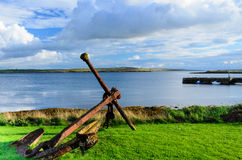 Old and rusty anchor from warship on shore Stock Images