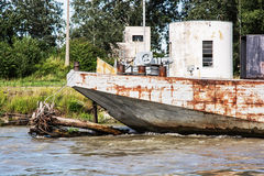 Old rusty anchored boat by riverside Royalty Free Stock Image