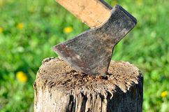Old rusty ax stuck in a dry wooden log Stock Photo