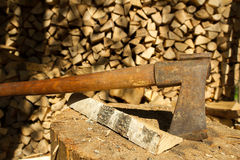 Old rusty axe. Old handmade axe and birch firewood Royalty Free Stock Photo