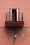 Old rusty balcony. And street lighter by pink brick wall Stock Photography