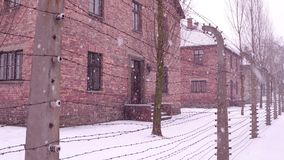 Old rusty barbed wire fence of Auschwitz Birkenau concentration and extermination camp. Brick barracks in falling snow Stock Photos