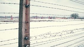 Old rusty barbed wire fence and distant ruined barracks of concentration camp in the snow. 4K steadicam shot
