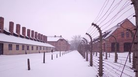 Old rusty barbed wire fences and concentration camp buildings. Brick barracks, lonely man in falling snow. Old rusty barbed wire fences and concentration camp Stock Images