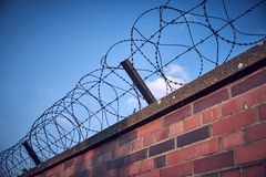 Old and rusty barbed wire on top of a bricked wall running diagonally from corner to corner of the frame stock photos