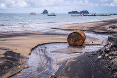 Old rusty barrel oil on beach in Asia. Rusty barrel oil on a partly black coloured beach illustrates the pollution of environment by oil spills. Longtail boats Royalty Free Stock Photography