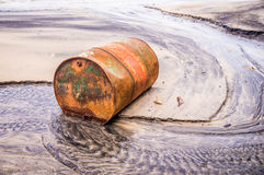 Old rusty barrel oil on beach. Rusty barrel oil on a partly black coloured beach illustrates the pollution of environment by oil spills Stock Photo