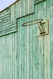 Old rusty basketball hoop without net on a green painted wooden wall stock photos