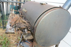 Old rusty BBQ smoker sitting outside. That hasn`t been used in years with leaves piling up Royalty Free Stock Image