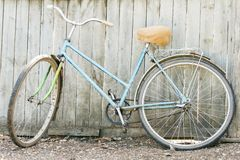Old rusty bicycle of near wooden fence. Vintage rustic style Royalty Free Stock Photography