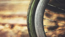 Old rusty bicycle wheel against warm blur background. Retro effect Royalty Free Stock Photography