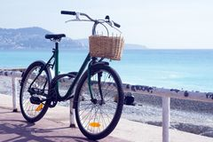 Old rusty bicycle with a wicker basket on the background of the turquoise sea. stock photo