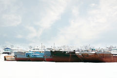 Old and rusty big freight ships on frozen river at winter Stock Photography