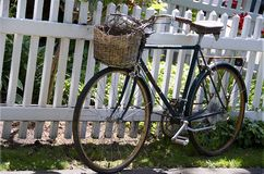 Old rusty bike leaned to the white fence Royalty Free Stock Image