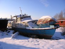 Old rusty boat moored to the shore in the winter froze on the river. Old abandoned rusty boat moored to the shore in the winter froze on the river stock image