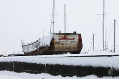 Old rusty boat in the snow royalty free stock image