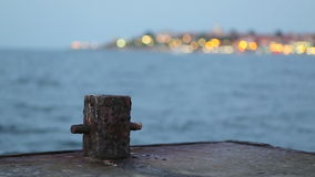 Old rusty bollard and city lights stock video footage