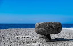 Old rusty bollard on a pier by the sea in Greece royalty free stock image