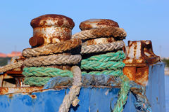 Old rusty bollard with rope on a vessel Royalty Free Stock Images