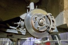 Old and rusty brake disc of the car under repair in the garage.  stock photos