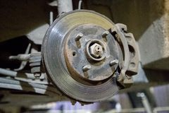 Old and rusty brake disc of the car under repair in the garage.  royalty free stock image