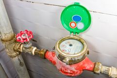 Old rusty brass valve with tubes and water meter. stock photography