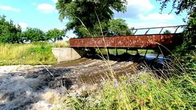 Old rusty bridge over a creek with a stormy water stock video footage
