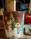 Old Rusty Bucket Painted With Snowmen. An old rusty bucket painted for Christmas with two snowmen and Christmas trees with snowflakes. One snowman has a red stock images