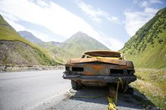 Old rusty burned car on the roadside of Georgia, surrounded by mountains and beauty stock image