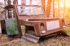 Old rusty car. Close-up of an old rusty jeep car with a broken door and no wheels on the background of a green coniferous forest Royalty Free Stock Photos