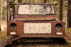 Old rusty car. Close-up of an old rusty jeep car with a broken door and no wheels on the background of a green coniferous forest Stock Photography
