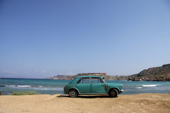 Old rusty car parked by the beach. An old green rusty Austin is parked on a scenic beautiful beach Royalty Free Stock Photography