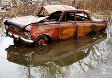 An old rusty car in a puddle arrived royalty free stock photography