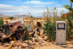 Old and rusty car wreck at a vintage gaz station Stock Images