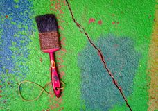 Carpenters paint brush. Old rusty carpenters paint brush on colorful dusty cracked concrete surface floor royalty free stock photos