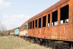 Old rusty cars standing in the abandoned depot. On the background of blue sky Royalty Free Stock Photography