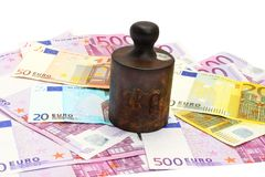 Old rusty cast-iron weight and money stock image