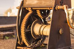 Old rusty chain gear wheels mechanism. Old industrial rusty chain, steel cable and gear wheels mechanism used for moving heavy stuff around Stock Image